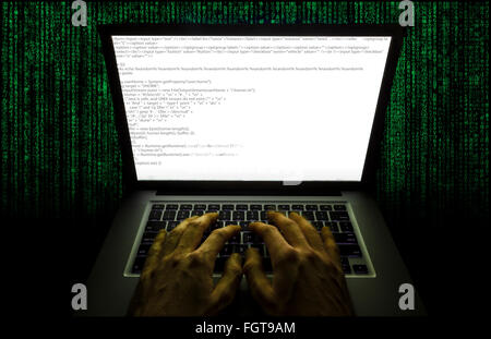 Moving hands at a laptop typing code - Stock Photo