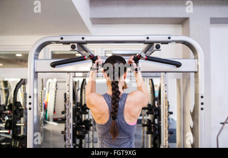 Woman in gym flexing back muscles on cable machine - Stock Photo