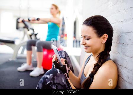 Fit woman in gym holding smart phone, brick wall - Stock Photo