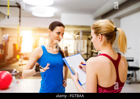 Woman in gym, personal trainer, consultiing plan on clipboard - Stock Photo