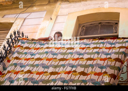 Daily life in Cuba - Cuban woman looking down over sheet hung out to dry on balcony at Havana, Cuba, West Indies, - Stock Photo