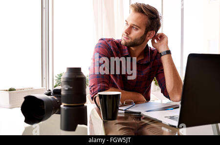 Entrepreneurial photographer looking off camera at his desk - Stock Photo