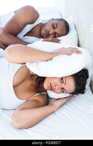 Disturbed wife sleeping besides snoring husband - Stock Photo