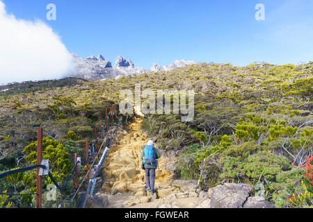 Solo hikers seen on Mount Kinabalu trails.Mount Kinabalu is the most visited mountain in Borneo. - Stock Photo