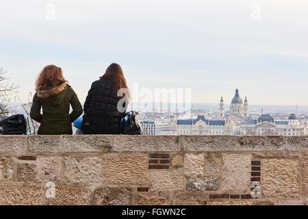 BUDAPEST, HUNGARY - FEBRUARY 02: Two girls sitting on wall enjoying the view from Buda Castle, with Gresham Palace - Stock Photo
