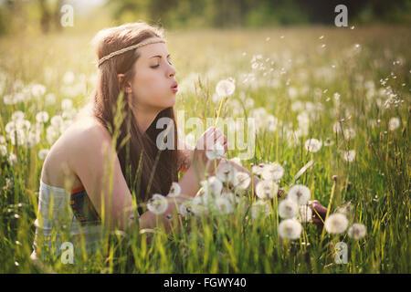 Beautiful hippie woman blowing dandelion flowers. Nature harmony - Stock Photo