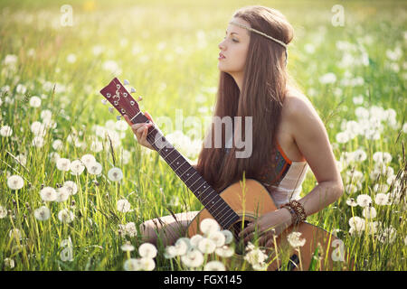 Hippie woman with guitar in summer meadow . Nature harmony - Stock Photo