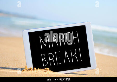 a tablet computer with the text march break written in it on the sand of a beach - Stock Photo