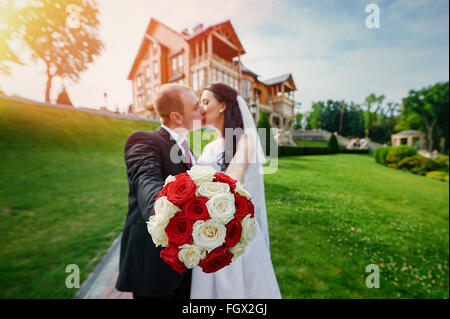 European bride and groom kissing in the park near house - Stock Photo