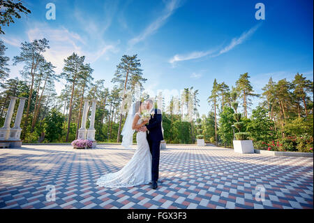 elegant stylish groom with his happy gorgeous bride kisses in the park - Stock Photo