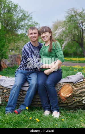 husband and his pregnant wife sitting on a wooden deck - Stock Photo