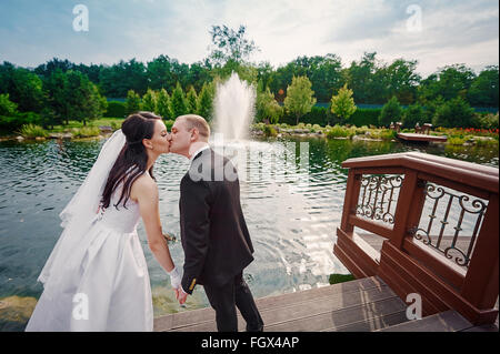 groom and the bride walk near the lake on their wedding day - Stock Photo