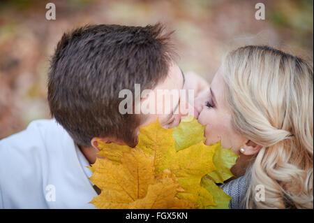 loving couple kissing in autumn park - Stock Photo