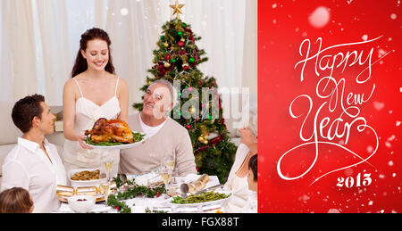 Composite image of mother showing turkey to her family for christmas - Stock Photo