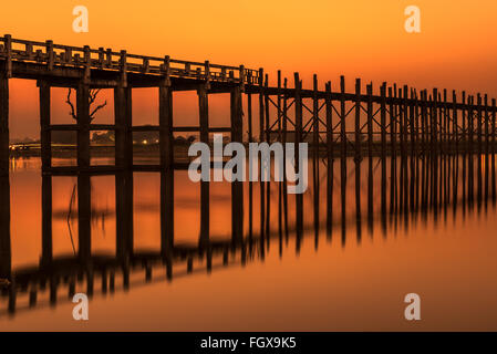 Sunset over the historic wooden U Bein Bridge near Mandalay in Myanmar. Long exposure. - Stock Photo
