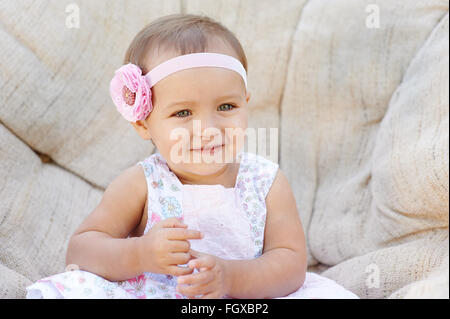 Little baby girl poses on a white chair.  She is smiling happily - Stock Photo