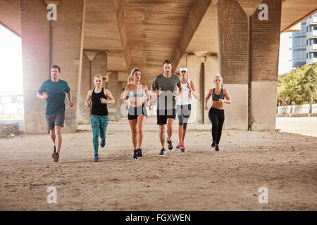 Portrait of group of healthy young people running together in city. Running club members training together in morning - Stock Photo