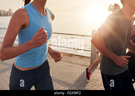 Cropped shot of young people running along seaside at sunset. Closeup image of group of runners working out on a - Stock Photo