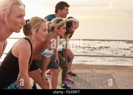 Runners standing on the line at the start of a race. Group of young people training for marathon race on road by - Stock Photo