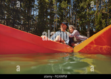 Active senior couple in two single kayaks side by side, with woman showing something interesting to man. Mature - Stock Photo