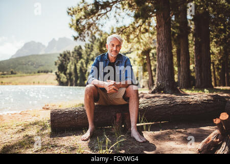 Portrait of relaxed mature man sitting on a wooden log near the lake. Mature man enjoying a day at the lake. - Stock Photo