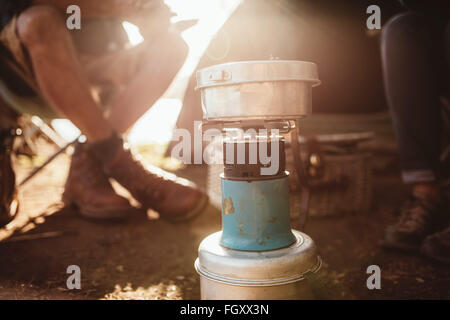 Close up portrait of a camp stove with couple sitting in background. - Stock Photo