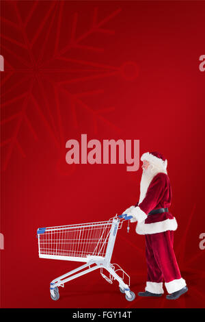 Composite image of santa pushes a shopping cart - Stock Photo