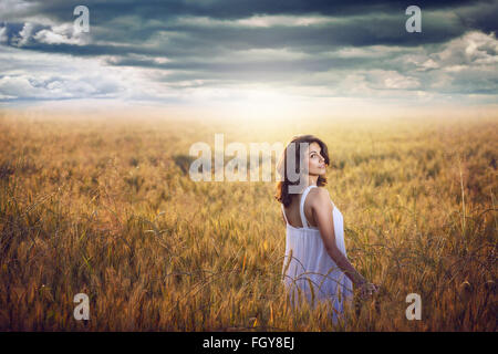 Beautiful woman in a corn field with dramatic sky . Sunset light - Stock Photo