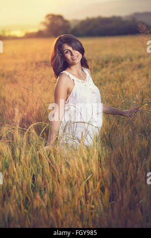 Beautiful woman poses in a field at sunset. Summer season portrait - Stock Photo
