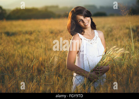 Beautiful smiling woman in a golden field at sunset. Summer season portrait - Stock Photo