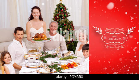 Composite image of family celebrating christmas dinner with turkey - Stock Photo