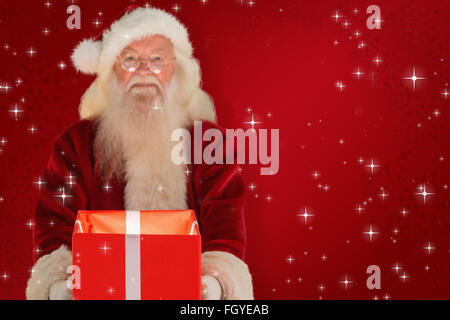 Composite image of father christmas offering a magical christmas gift - Stock Photo