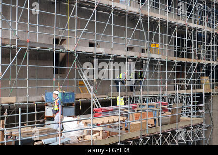 Men at work on a scaffolding to a tall building project in Bristol, England, UK GB - Stock Photo