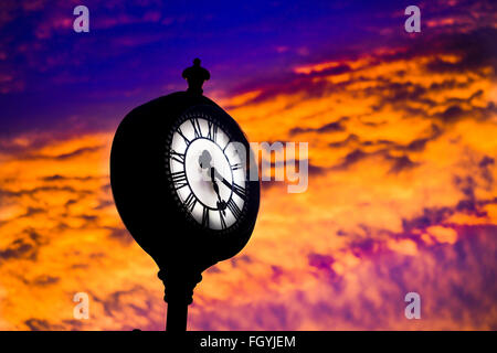Public clock against a strong sunset showing the time on a roman numeral face of quarter past five. - Stock Photo