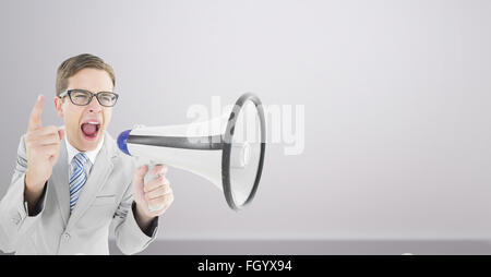 Composite image of geeky businessman shouting through megaphone - Stock Photo