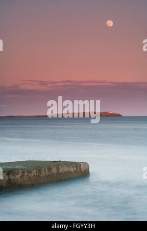 Trial island with the moon rising over it. - Stock Photo