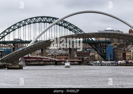 A pleasure craft sails down the Tyne as the Gateshead Millennium Bridge is raised, with the Tyne Bridge in the background - Stock Photo