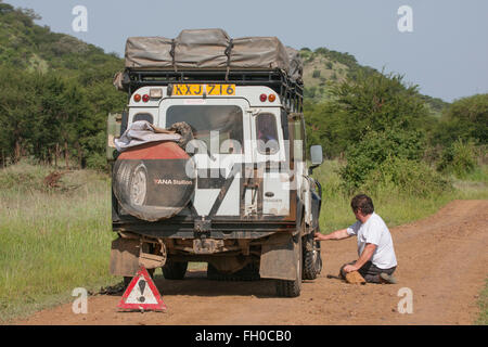 Rough tatty old Land Rover Defender 110  in the Serengeti  National Park Tanzania. Broken down - Stock Photo
