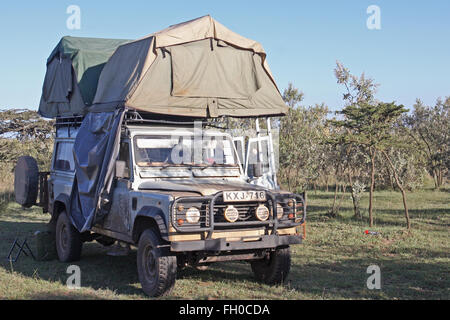 Old Land Rover Defender 110  Parked in a National Park Kenya. Roof tents pitched - Stock Photo