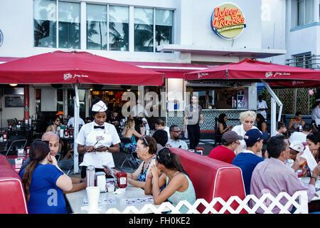Miami Beach Florida Ocean Drive New Year's Eve Johnny Rockets restaurant alfresco Black woman waitress order - Stock Photo