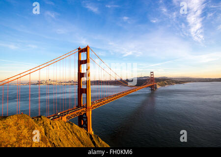 Sunny blue skies over the San Francisco skyline with the iconic Golden Gate Bridge - Stock Photo