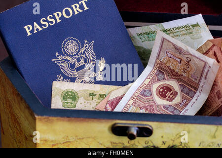 A US passport with foreign currency - Stock Photo