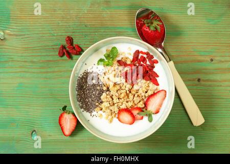 healthy breakfast of muesli, yoghurt, chia seeds, fruit and goji - Stock Photo