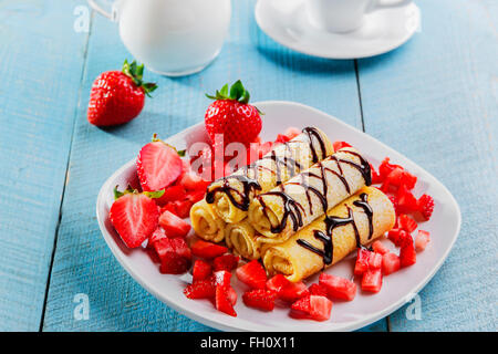 rolled pancakes with strawberries and chocolate breakfast - Stock Photo