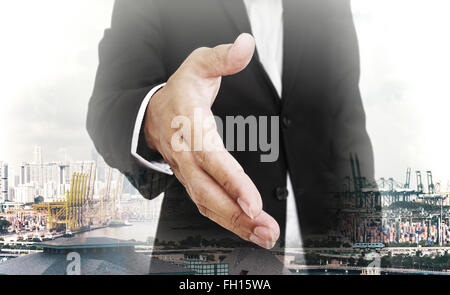 Businessman extending hand with capital city background, selective focus, shallow depth of field - Stock Photo