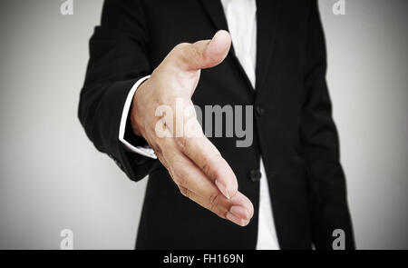 Businessman extending hand, selective focus, shallow depth of field - Stock Photo