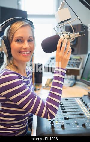 Portrait of happy female radio host broadcasting - Stock Photo