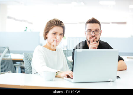 Two thoughtful young business people sitting in the office and using laptop together - Stock Photo