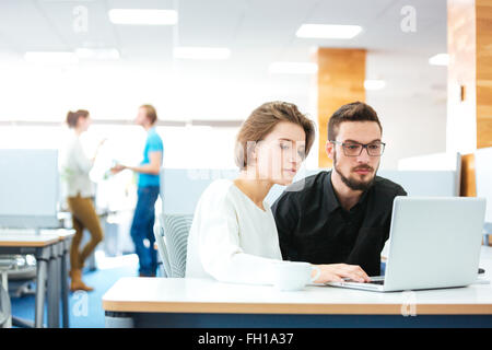 Serious focused young man and woman sitting and working with laptop together in office - Stock Photo