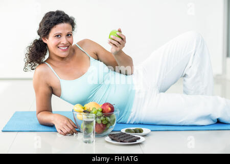 Portrait of pregnant woman holding an apple - Stock Photo